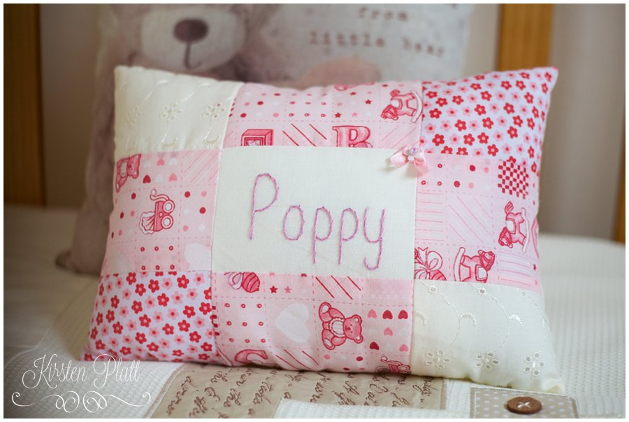 Pink embroidered cushion with the name Poppy