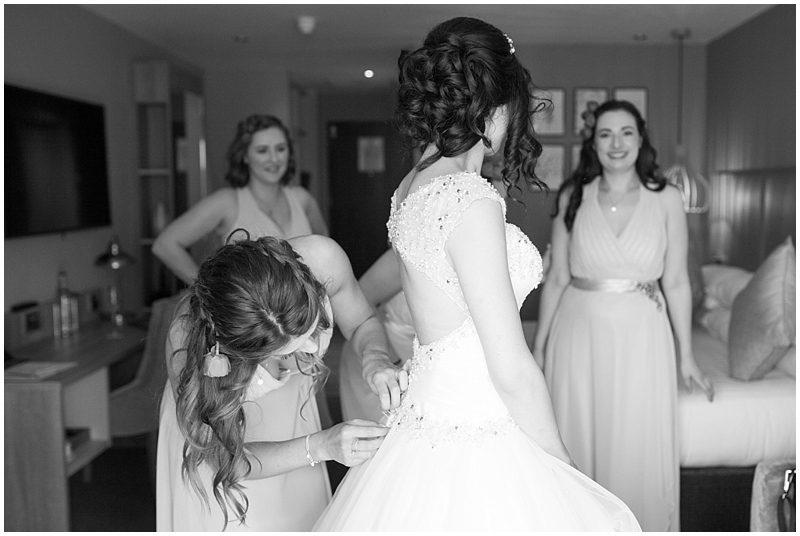 Bridesmaids help the bride get ready
