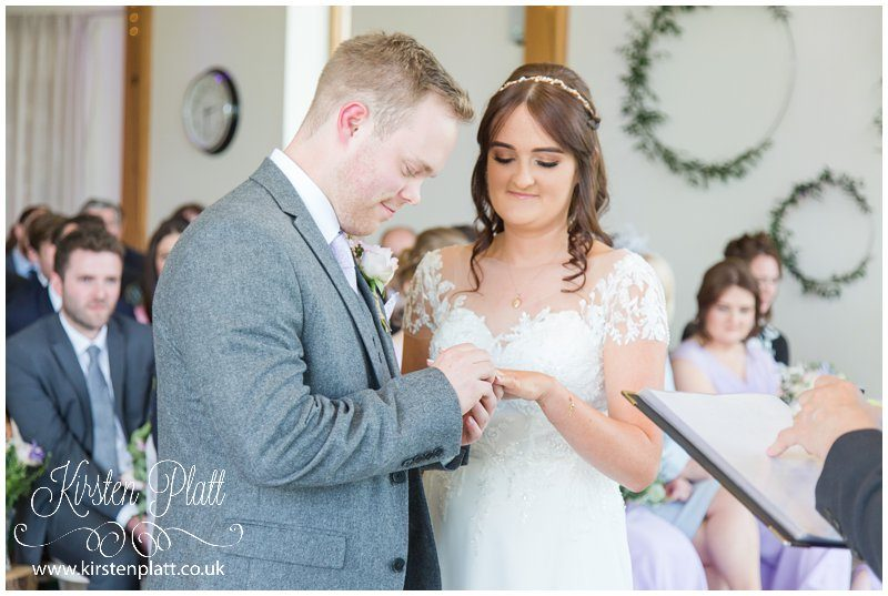 The groom putting a wedding ring on the brides finger
