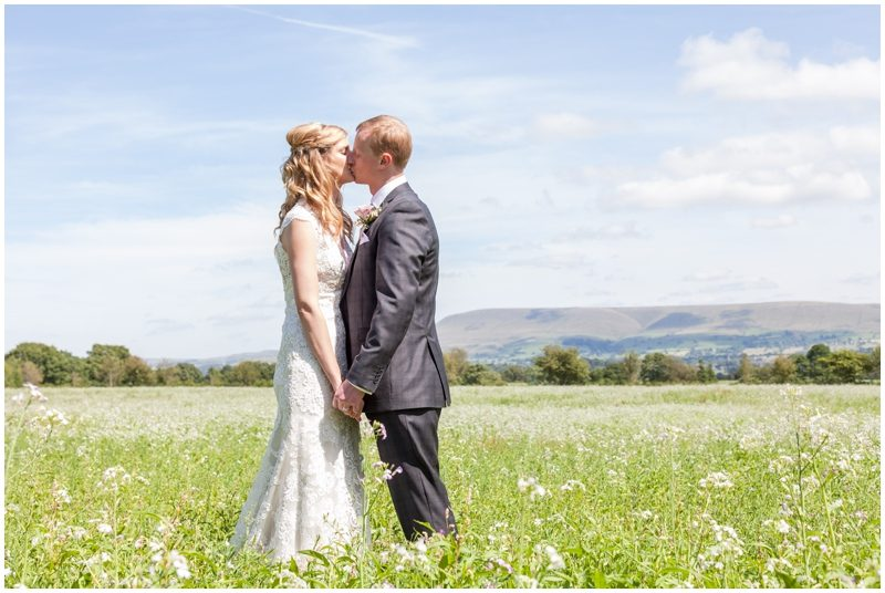 Bride and groom kissing in a meadow